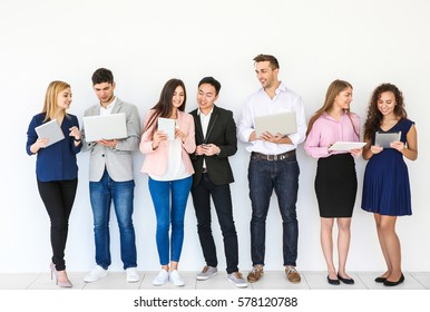 People with gadgets standing near light wall