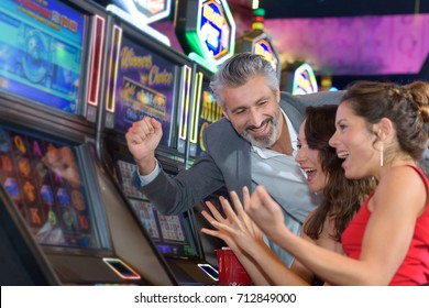 people gambling in a casino playing slot machine