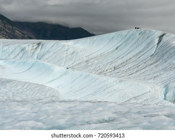 People give scale to the size of Root Glacier while they are standing on top of ice ridge.