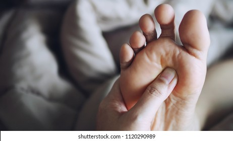 People giving a foot reflexology treatment together at home. Exchange foot massages with a friend or loving couple for stress relieving concept. (close up, selective focus, space for text or article)