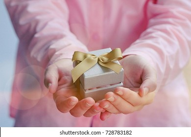 People giving a gift closeup soft focus blur background