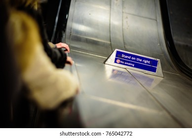People going down escalator inside London underground. Stand on the right warning sign.