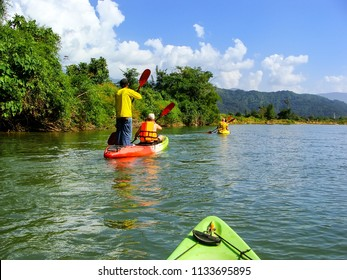 People going down Nam Song River in kayaks near Vang Vieng, Vientiane Province, Laos. Kayaking is a popular tourist activity in Vang Vieng.