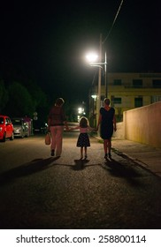 People going down the street at night.