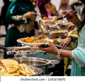 People grabbing food from buffet table in the banquet hall