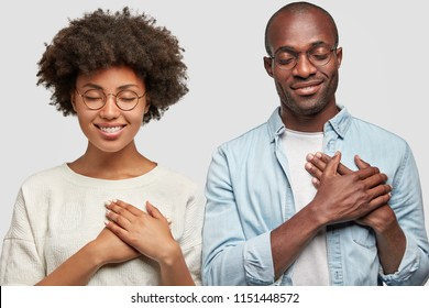 People and gratitude concept. Horizontal shot of pretty young African American female and dark skinned male keep hands on chest, being thankful to people who helped them, have charming smiles