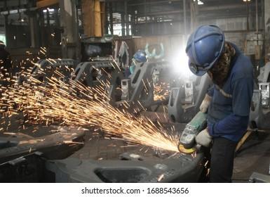 people grinding metal in room