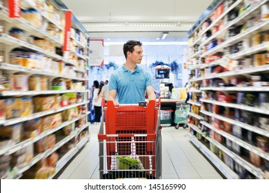 people in grocery  store, man walking with shopping cart in supermarket