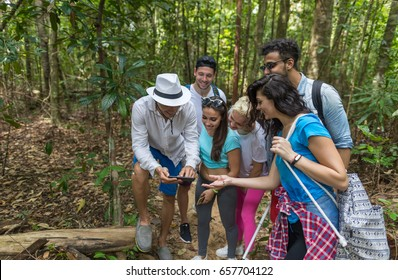 People Group With Backpacks Trekking On Forest Path With Giude Using Cell Smart Phone, Mix Race Young Men And Woman On Hike Tourists Adventure Activity