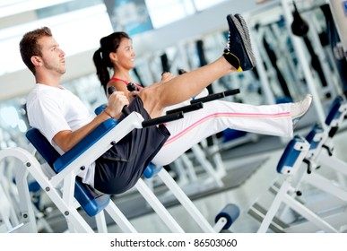 People at the gym exercising their abs on a machine