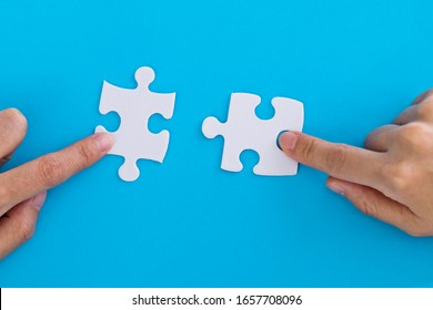 People hand connect two couple puzzle pieces.