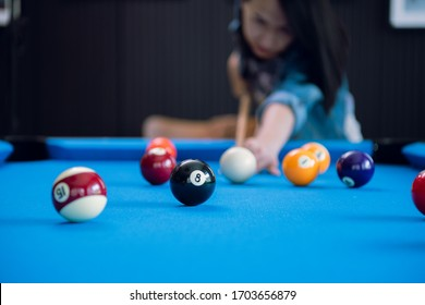 People hand and Cue arm playing pool game or preparing aiming to shoot ball on a blue pool table at home