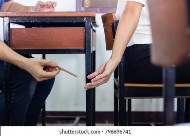 People hand handing pencil to to person in the front seat