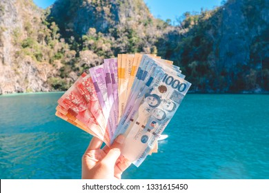 People hand hold many of various value  Philippines peso banknote when travelling in Coron Islands .