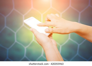 people hand hold and touch screen smart phone on soccer goal net background.