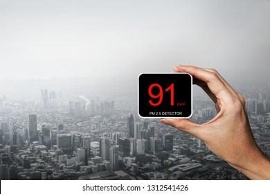 Menschen Hand halten PM 2,5 Detektor über Smog Stadt aus PM2,5 Staub. Stadtlandschaft von Gebäuden mit schlechtem Wetter von Fine Partikel Matter. Luftverschmutzung, ungesundes Konzept für den Hintergrund, Kopienraum.