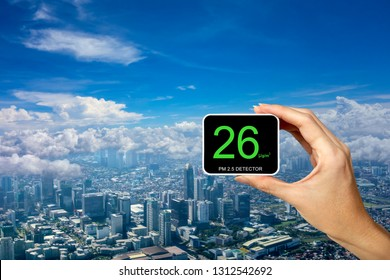People hand holding PM 2.5 Detector showing 26 microgram over city with cloud and clear blue sky. Cityscape of buildings with good air quality. Air pollution concept for background, copy space.