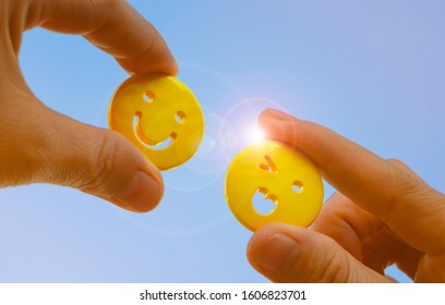 people hand holding yellow emoticon smiley face icon symbol on blue sky background with copy space, for a positive mindset in business marketing and beautiful world peace concept