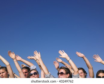 People with hands in the air, with only their faces visible. Horizontal.