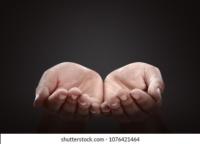 People hands with pray gesture over black background