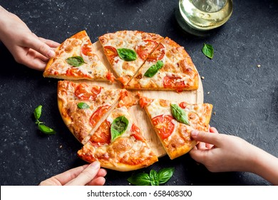 People Hands Taking Slices Of Pizza Margherita. Pizza Margarita and  Hands close up over black background.