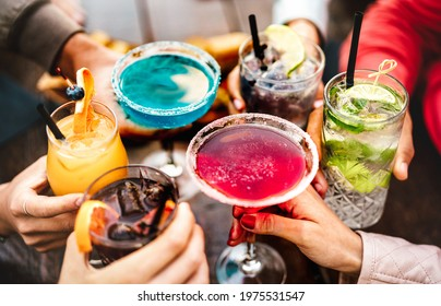 People hands toasting multicolored fancy drinks - Young friends having fun together drinking cocktails at happy hour - Social gathering party time concept on warm vivid filter - Shallow depth of field