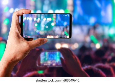 People hands use smart phones record video concert music festival live streaming video on internet to social media comment chat to Friend