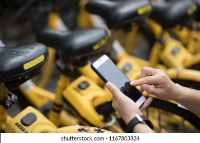People hands using smartphone scanning the QR code of shared bike in city