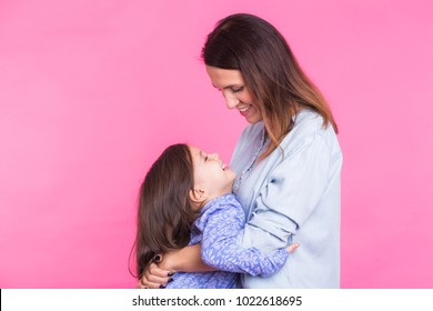 people, happiness, love, family and motherhood concept - happy little daughter hugging and kissing her mother over pink background
