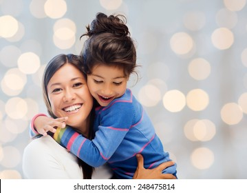 people, happiness, love, family and motherhood concept - happy mother and daughter hugging over holiday lights background