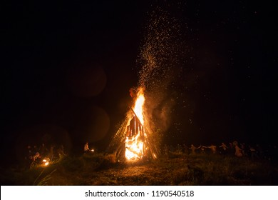 people are happy to have fun and dance in a round dance around a large fire warming them with flame at night at a multicultural ethnic festival, a lot of sparks and heat from burning wood