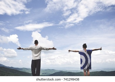 people happy standing on mountain with raised hands and looking