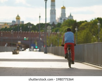 People have active sports activity on the Moscva river embankment in downtown area in hot spring day. Man cycling. Backs, rear view. Healthy lifestyle concept