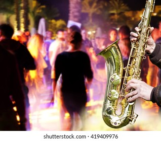 People have fun at night on a beach. music. jazz. saxophone.