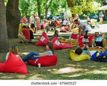 People have a snack and relax in the grass on beanbags at the Street Food Festival in central park CLUJ-NAPOCA ROMANIA - JUNE 9 2017. Picnic time.