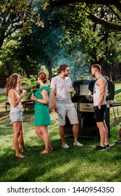 People having a barbecue grill party with drinks, food and cooking outdoor. Camping concept with friends and people