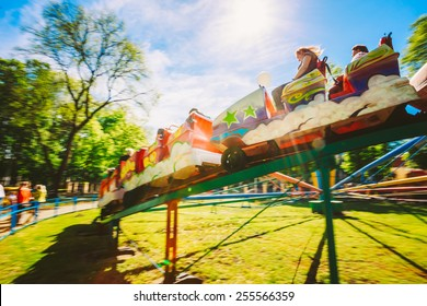 People Having Fun On Rollercoaster In The Park. Photo With Zoom Blur For Motion Effect