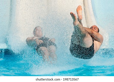People having fun, sliding at water park.