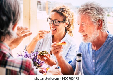 People having fun together during lunch in friendship - mixed ages woman and an eating in family activity - caucasian adults laugh and smile for nice activity