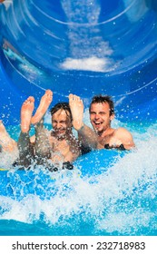 People having fun, water sliding at aqua park.
