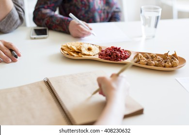 People Having Meeting And Eating Snacks in the office. Three colleagues having talk together at work. Creative team at the table