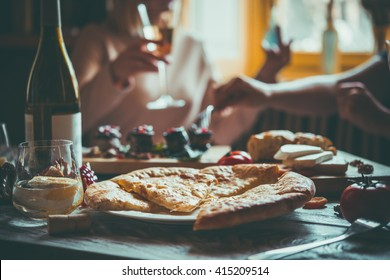 People are having traditional georgian lunch or dinner of khachapuri, aubergine rolls, imeretian and suluguni cheeses and wine served on wooden table. Toned image