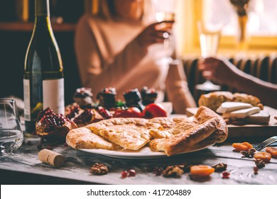 People are having traditional georgian lunch or dinner of khachapuri, aubergine rolls, imeretian and suluguni cheeses and wine served on wooden table.