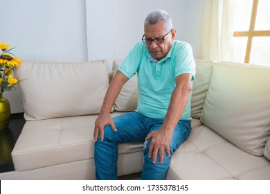people, health care and concept medical problem - unhappy older man suffering from leg pain at home