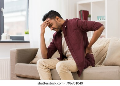 people, health care and problem concept - unhappy man suffering from pain in back or reins at home