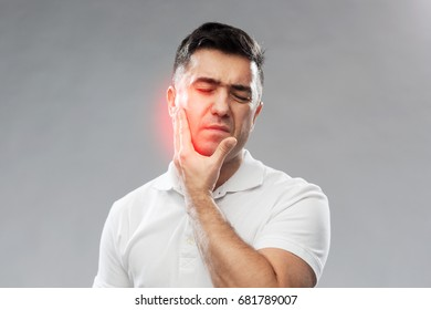 people, healthcare, dentistry and problem concept - unhappy man suffering toothache over gray background