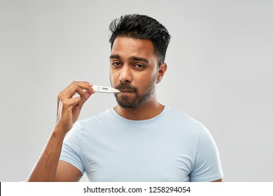 people, healthcare and fever concept - unhealthy indian man measuring oral temperature by thermometer over grey background