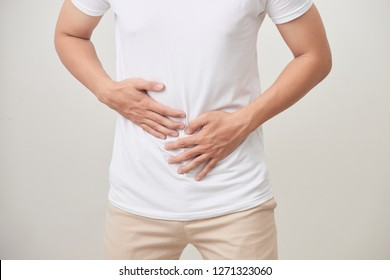 people, healthcare and health problem concept - unhappy man suffering from stomach ache over white background