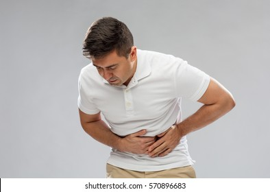 people, healthcare and health problem concept - unhappy man suffering from stomach ache over gray background