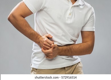 people, healthcare and health problem concept - close up of man suffering from stomach ache over gray background